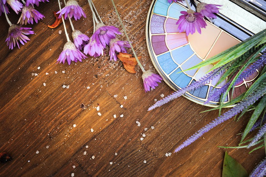 Flat lay eyeshadow palette and lavender flowers against wood background