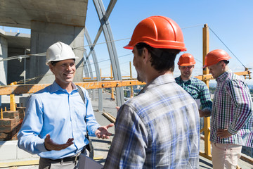 Builders Meeting On Construction Site Architect Talking With Contractor Over Group Of Apprentice Teamwork Concept