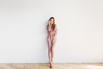 Thin elegance blond woman standing by white wall at full length Wall mural