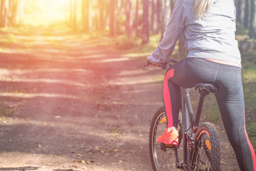 Woman riding a mountain bicycle along path at the forest