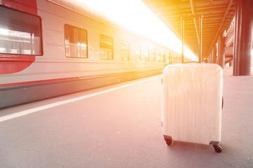 White travel suitcase on platform at railway station