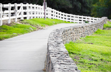 country road between a picket fence and a stone wall