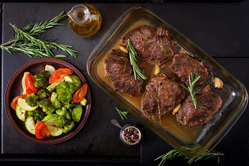 Baked beef steak with garlic and rosemary and vegetables. Flat lay. Top view