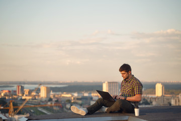Hipster with laptop on roof