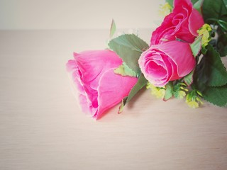 Deep pink artificial roses, vintage style background