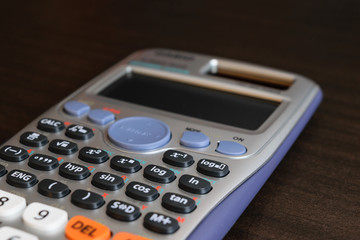 close up advance calculator for engineer or business/finance on the dark brown table table.