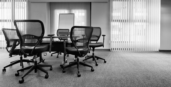 Ergonomic office chairs around a small conference table. Black and white with copy space. Banner format