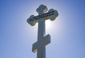 Orthodox cross against the blue sky and the sun. Cross in the backlight of the sun. Symbol of the Christian faith. The inscription on the cross: salvation and preservation
