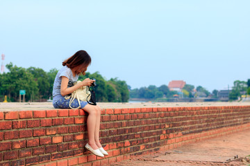 Young woman sitting on brick wall