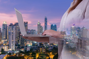 Multiple exposures of business concept with woman is using laptop and city skyline background.