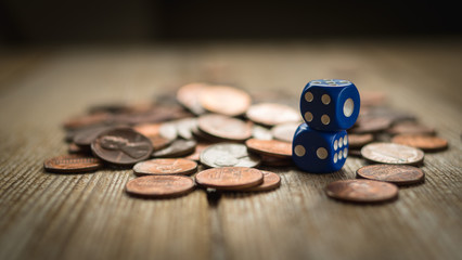 Dices and coin stack on wooden table