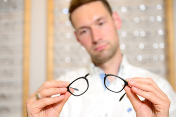 in optician shop- young man with broken glasses