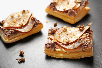 Delicious pastries with chocolate, pear and nuts on grey background