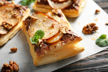 Delicious pastry with chocolate, pear and nuts on wooden table