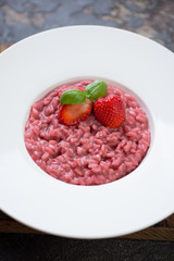 Close-up of strawberry risotto served in a white plate, selective focus, studio shot