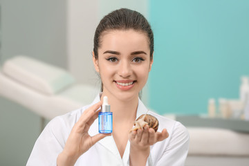 Young woman with giant Achatina snail and cosmetic product in beauty salon