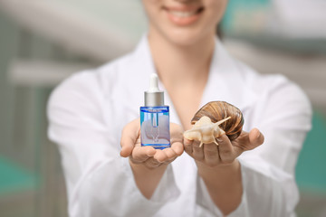 Young woman with giant Achatina snail and cosmetic product, closeup