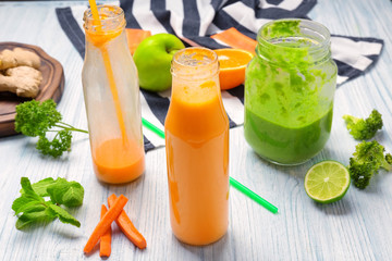 Fresh smoothies with ingredients on table
