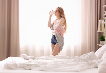Morning of beautiful young woman drinking coffee while standing near window at home