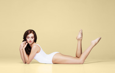 Fit and sporty girl in underwear. Beautiful and healthy woman posing over yellow background. Sport, fitness, diet, weight loss and healthcare concept.