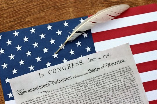 Declaration of Independence with American Flag on Wooden Table with White Pen