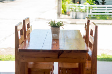 Brown wooden table with green flower in white pot in front of house with four chairs, soft focus.