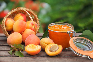 Wicker basket full of ripe apricots and apricot jam in a jar. Healthy diet food.
