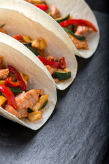 Mexican tacos with pork and vegetables. Al pastor taco on slate tableware. Close up.