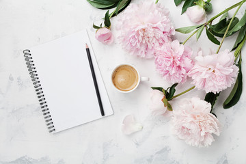 Morning coffee mug for breakfast, empty notebook, pencil and pink peony flowers on white stone table top view in flat lay style. Woman working desk. Wall mural