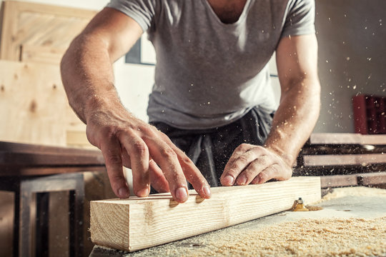 man  steals a wooden with a milling machine