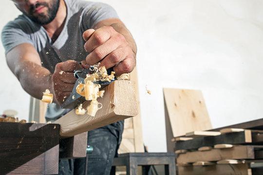 man handles a wooden bar with a black jack plane