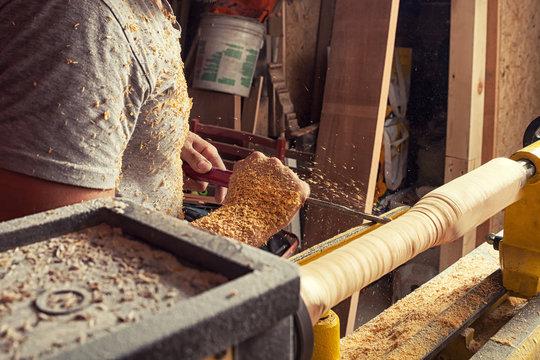 man processes a wood on a lathe