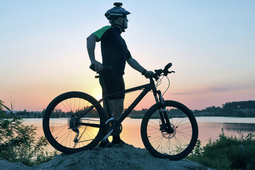 silhouette of a standing cyclist with bike at sunset