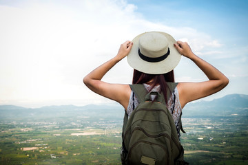 Relaxed happy traveler, Young Hipster woman traveler with backpack holding hat weave and looking at beautiful view nature mountain background