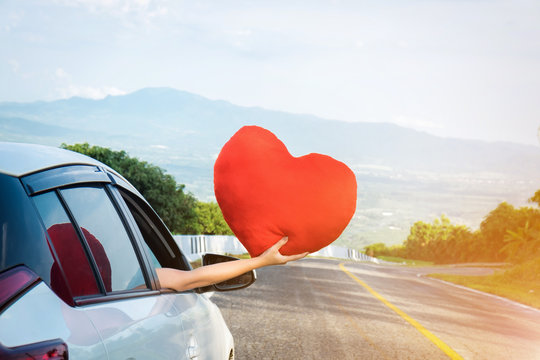 Relaxed happy traveler, Young beatiful asian gilr holding big red heart and Reach out of the car at sunset and beautiful view with mountain road background