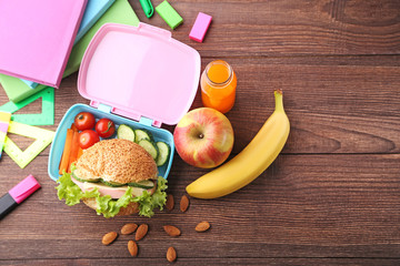 School lunch in box with apple and banana on brown wooden table