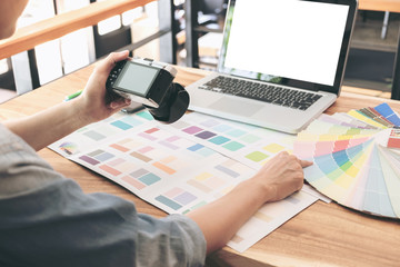 Color samples, colour chart, swatch sample, Graphic designer being selecting Color band and graphics tablet at workplace with work example in camera and laptop on wooden desk