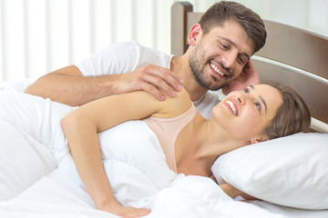 The man lay near a woman in the bed
