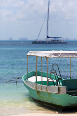 Old and rusty fishing boat on the shore. Turquoise water. Sailboat on the background out of focus.
