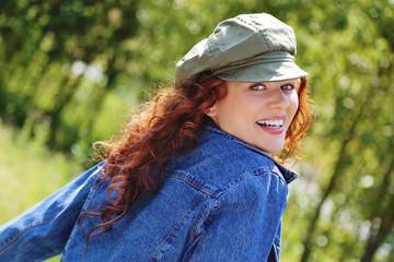 jolie femme rousse souriante dans nature avec casquette et jeans