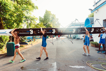 four athlete carrying canoe