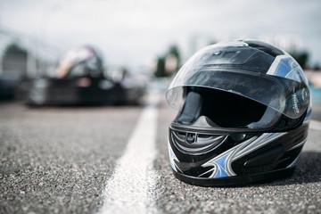 Racer helmet on asphalt, karting sport concept