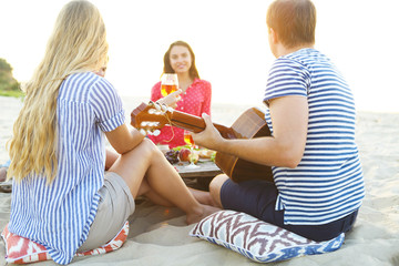 Young friends drinking rose wine on summer beach picnic