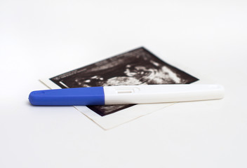 Plastic pregnancy test and ultrasound picture.