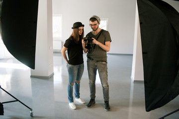 Photographer speaks with model on photoshoot. Man with camera show pictures to casual woman during the studio session. Production of commercials backstage