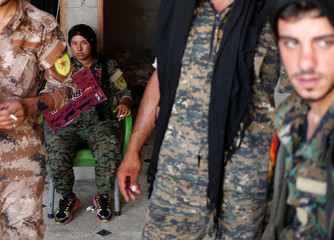 Kurdish fighters from the People's Protection Units (YPG) rest in a house in Raqqa