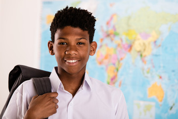 African boy in his school uniform and backpack