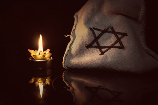 A burning candle next to the star of David