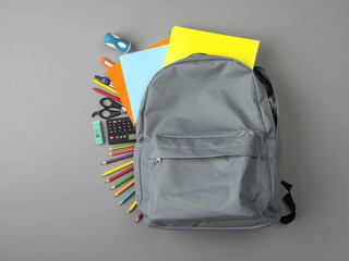 Top view of a backpack and school supplies on grey wooden table