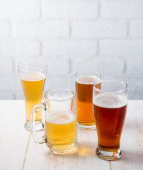 Beer glasses with various beer on wood table against white brick wall